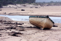 A lonely boat. A picture of an old lonely boat on a rainy day. The picture was taken at the lagoon in Plettenberg Bay in South Africa Royalty Free Stock Images