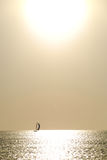 Lonely boat against the sun Royalty Free Stock Image
