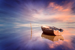 Lonely boat and amazing sunset at the sea Stock Images
