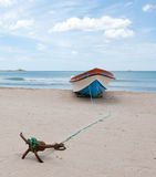 Lonely boat on beach. Lonely boat painted in bright colors on the beach Royalty Free Stock Images