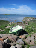 Lonely boat on the beach amond the stones. Fishing boat Stock Photo