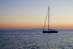 Lonely boat on a calm sea. Lonely boat sailing on the calm sea at sunset Greece royalty free stock photography