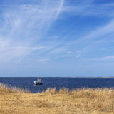 Lonely boat and calm sea. Lonely boat standing against calm sea landscape Stock Photo