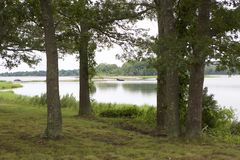 A Lonely Boat in the Distance. An empty row boat in the distance, framed by mature, green trees. Grassy ground. Body of calm, serene waters in the center Royalty Free Stock Photography