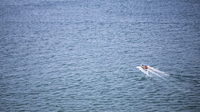 A Lonely boat floating out into the open ocean. A Lonely boat floating out into the open sea royalty free stock photos