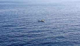 A lonely boat in the huge blue sea stock image