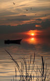 Lonely boat in lake. Beautiful boat at sunset in the lake Royalty Free Stock Photo