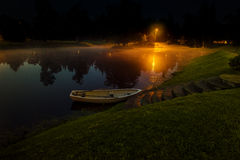 Lonely boat on lake with fog. At night time Stock Images