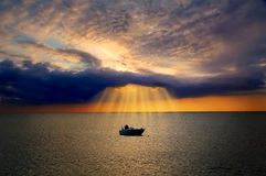 Lonely boat lit by divine light from cloud. Lonely boat floating in sea is lit by divine light from dark cloud during sunset Royalty Free Stock Images