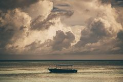 A covered anchored motorboat, dramatic sunset. A lonely boat is lying at anchor in the open sea during the evening with a stunning cloudscape above on the sunset stock photos