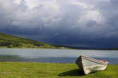 Lonely boat near the lake. With storm comming at the background royalty free stock images