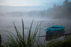 Lonely boat on a peaceful lake. Foggy autumn sunrise twilight. Bright blue turquoise shallop quiet forest, swamp plants. Smoke mist on still calm water. Russia stock photos
