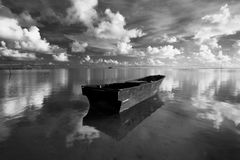 Lonely boat with reflection of clouds and sky royalty free stock images