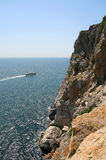 Lonely boat with rock and beautiful blue sky. The rock with boat near Yalta, Crimea Royalty Free Stock Image