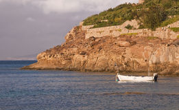 Lonely boat at the rocky cliffs azure sea Stock Image