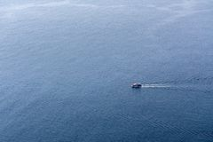 Lonely small boat sailing in the sea. stock photos