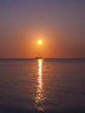Lonely boat sails on sea. At sunset Royalty Free Stock Photos