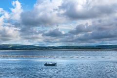 Boat in blue sea against cloudy sky. Lonely boat in the sea against cloudy sky in the autumn Stock Photo