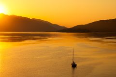 Lonely boat in the sea on sunrise Stock Images