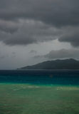 Lonely boat in the storm. Coast line and black clouds in the bac Stock Image