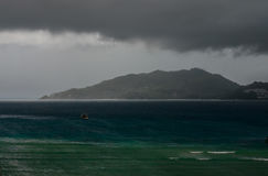 Lonely boat in the storm. Coast line and black clouds in the bac Royalty Free Stock Photos