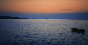 Lonely boat in sunset. A romantic view on the sunset, it works calmly and harmoniously. Take time and enjoy infinity Royalty Free Stock Photo