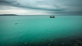 Lonely boat on turquoise water under dark sky royalty free stock image