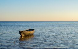 Lonely boat in the water - peaceful evening seaside. Background royalty free stock photo