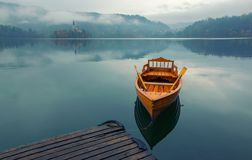 Lonely boat on the water surface of Bled lake, Slovenia. Lonely boat on the water surface of Bled lake at foggy autumn day, Slovenia stock photo