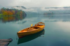 Lonely boat on the water surface of Bled lake, Slovenia. Lonely boat on the water surface of Bled lake at foggy autumn day, Slovenia royalty free stock photos
