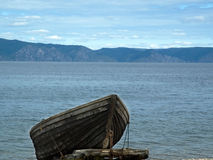 Lonely boat. Wooden boat on the beach  on a sky background of mountains and water Stock Photography