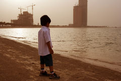 Lonely boy on the beach. Boy watching on the beach alone royalty free stock photos