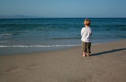 Lonely boy on the beach Stock Images
