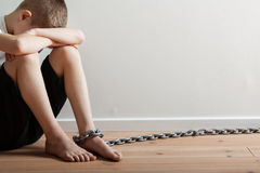 Lonely Boy with Chain on his Foot Hiding his Face Royalty Free Stock Photo
