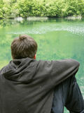 Lonely boy on green river Stock Photos