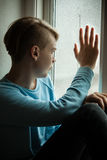 Lonely boy looking out of window Royalty Free Stock Image