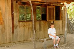 Lonely Boy at Old Cabin Stock Photography