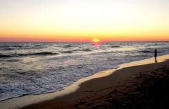 Lonely boy on the seashore during a sunset. Stock Photography