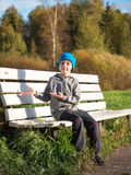 Lonely boy sitting on a bench in a cap and jacket Royalty Free Stock Photos