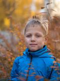 Lonely boy with a smile in autumn Park royalty free stock photos