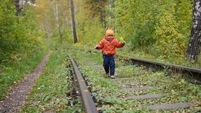 A lonely boy walking on the railroad tracks. Dangerous games and entertainment. Autumn day. A lonely boy walking on the railroad tracks.. Autumn day stock video footage
