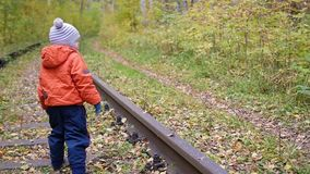 A lonely boy walking on the railroad tracks. Dangerous games and entertainment. Autumn day. A lonely boy walking on the railroad tracks.. Autumn day stock video