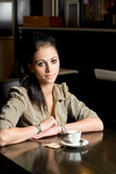 Lonely brunette in a coffee shop. Stock Images