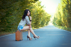 Lonely brunette girl sits on an old suitcase in the middle of th Stock Image