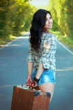 Lonely brunette girl smiling and holding an old suitcase in the Royalty Free Stock Photos