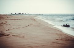 Lonely and bucolic beach in Hawaii, US. Bucolic scene of an empty beach in Hawaii, bathed by the waves of a calm sea and hazy background. US royalty free stock image