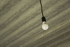 Lonely bulb hanging on the wire from the grey concrete ceiling. Construction concept background stock photography