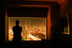 Silhouette of man at window. The silhouette of a man with arms crossed in front of a window with a view over a city lit in the night Royalty Free Stock Photos