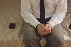Lonely businessman in hotel room sitting on the bed Royalty Free Stock Photography