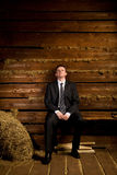Lonely businessman sitting on bench near haystack. In wooden log hut Royalty Free Stock Photos